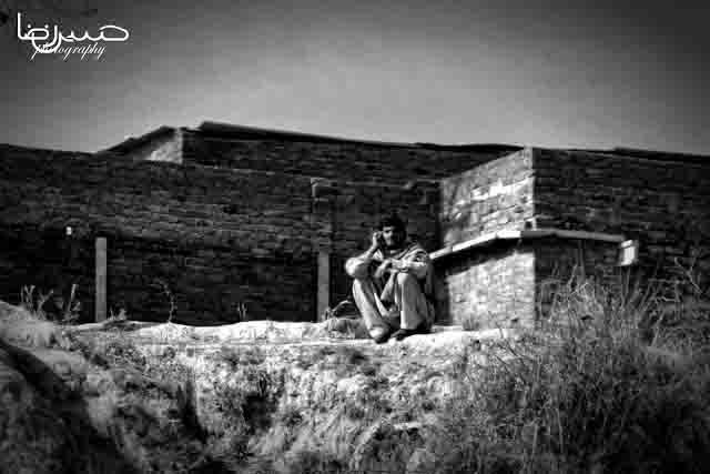 Pakistani village man sitting on mound