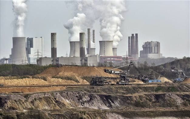 In this April 3, 2014 file photo giant machines dig for brown coal at the open-cast mining Garzweiler in front of a smoking power plant near the city of Grevenbroich in western Germany. (Credit: AP) Click to Enlarge.