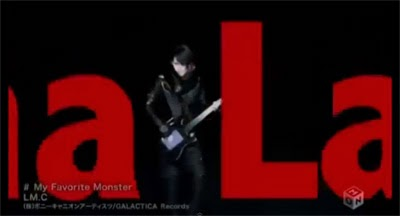 Aiji plays guitar against a black background while the words Sha la la la la la la la go past.