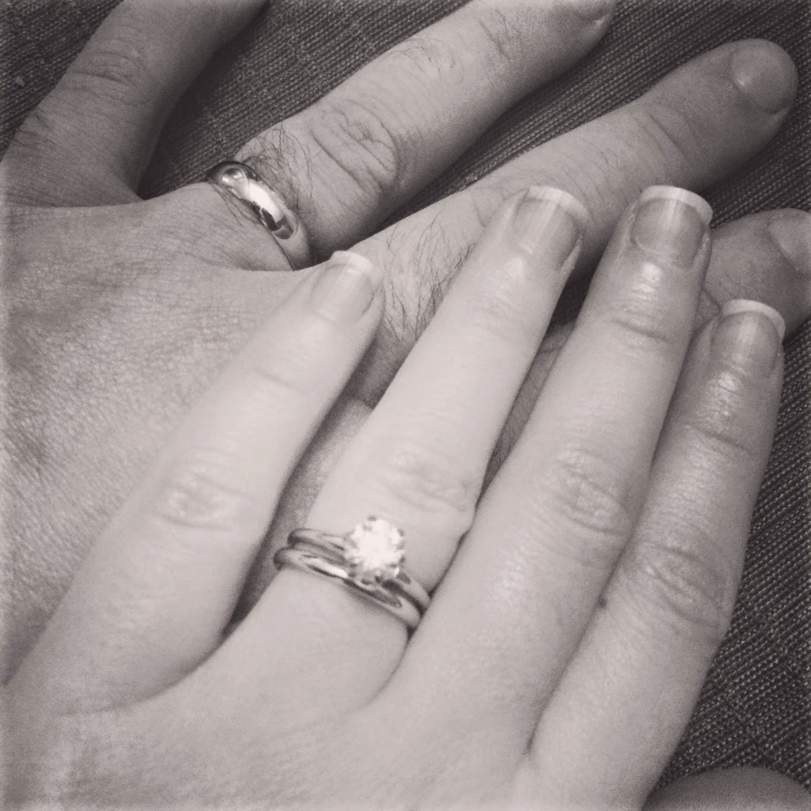 a picture of hands with wedding rings in black and white