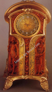 A boxwood clock designed and carved by Edmond-Henri Becker, with mount and chasing by Alfred Menu, originally made in 1900. The decorative details symbolize night and day.