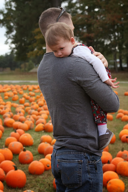 Daddy holding tired Maddie at the pumpkin patch