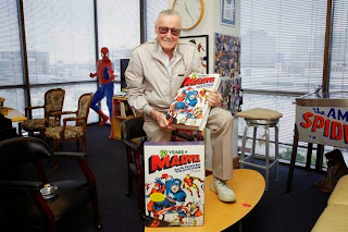 Stan Lee holding 75 Years of Marvel Comics: From the Golden Age to the Silver Screen hardcover book by Roy Thomas and Josh Baker