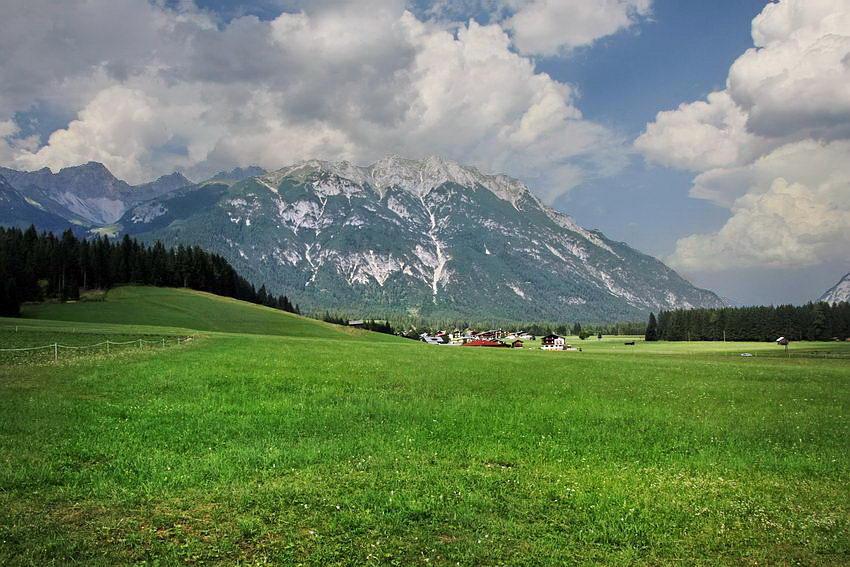 Campo aberto com erva e pequenas plantas ladeado por floresta de coníferas. Ao fundo uma pequena povoação com a arquitectura típica da região e por fim, uma montanha com o cume preenchido por rochas. Céu azul, com nuvens a descerem sobre os montes