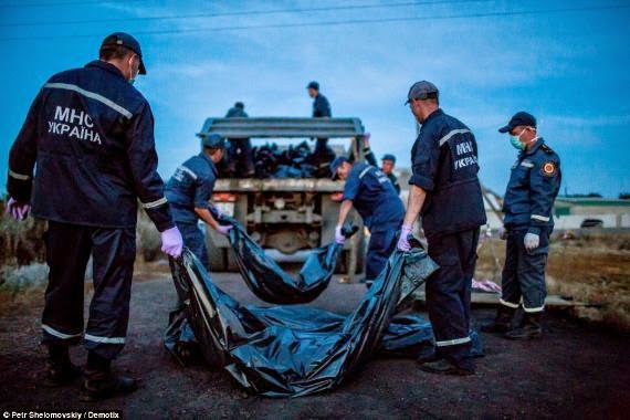 Bodies of MH17 crash victims tossed into rubbish trucks and taken to morgue train after 3 days laying in field