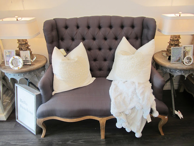 Pom Pom Interiors Settee love seat with tufted back, two white pillows, a white knit throw, two vintage inspired side tables with reclaimed wood tops and matching lamps