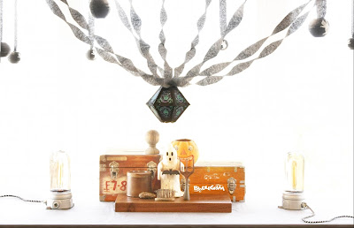 A vintage-style Halloween display of black crepe paper with a Bindlegrim lantern, also with refurbished lighting, wooden boxes, and vintage pumpkin