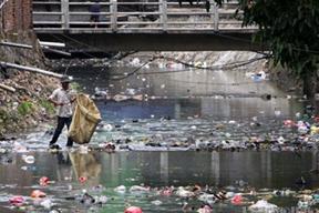 Kegiatan manusia membuang sampah dan limbah industri