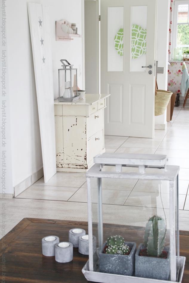 Blick vom Wohnzimmer mit Kakteen unter Glas zur Kommode im Esszimmer mit pastelligen Wohnaccessoires hin zur Küche mit geblümter Tapete für westwing style trip