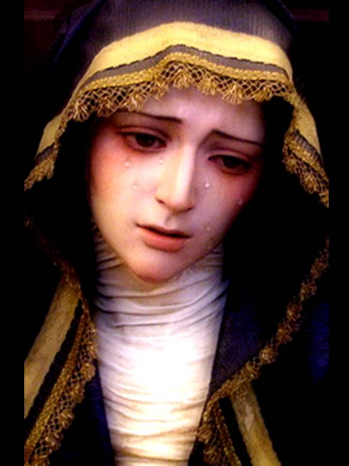 La Virgen con una toca negra y bordes dorados. Está llorando.