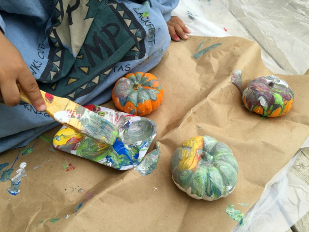 toddler painting pumpkins