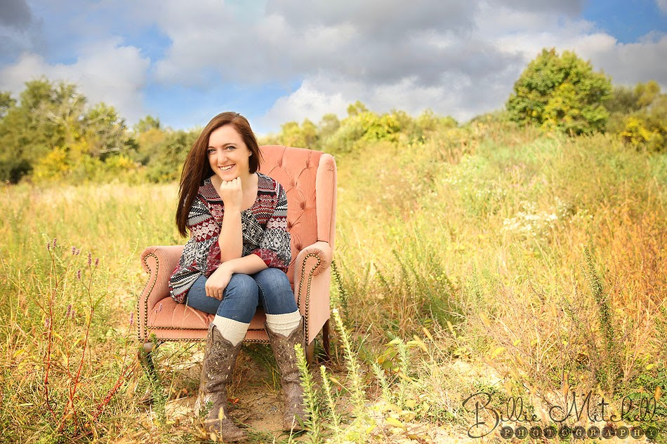 teen girl sitting in antique pink chair in a field