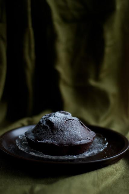 finom kakaós muffin porcukorral megszórva, üvegtányéron, zöld háttér előtt
