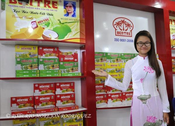 Joven usando un traje típico de Vietnam muestra productos de su país durante la inauguración del pabellón de esa nación del Asia en la XXXI Feria Internacional de La Habana, FIHAV 2013
