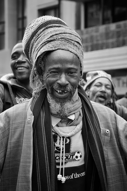 a rastafarian smiles warmly in this south african street portrait