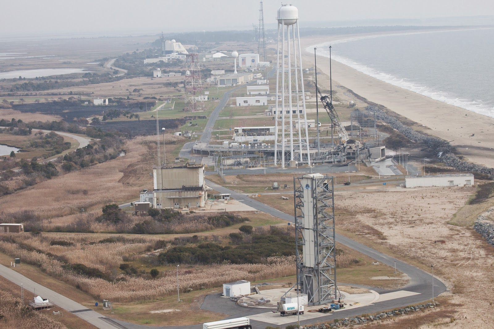 An aerial view of the Wallops Island launch facilities taken by the Wallops Incident Response Team Wednesday, Oct. 29, 2014 following the failed launch attempt of Orbital Science Corp.'s Antares rocket Oct. 28, Wallops Island, VA. Photo Credit: NASA/Terry Zaperach