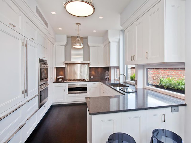 The white kitchen in an apartment has white cabinet and drawers with long drawer pulls, black counter tops, clear Kartell Lucite purple bar stools, stainless appliances and two pendant lights