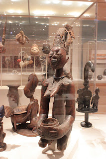 A photograph of a series of large African sculptures carved in wood.