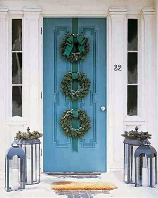 Metalowe lampiony i świąteczne stroiki na drzwiach