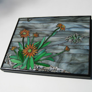 Mixed-media mosaic wall art piece depicting a beautiful weed growing in old, cracked concrete.