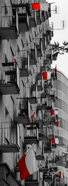 Blog przy Alei niepodległości na którego balkonach mieszkańcy zawiesili flagi narodowe