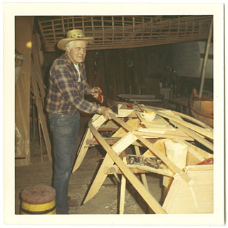 Image: 3.5 x 5 inch, color photographic print. Grunwald is standing next to a boat he is framing. He has a saw in his hand and is looking at the camera.
