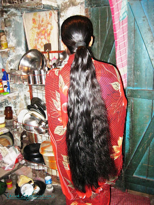 Oiled long hair made as pony tail.