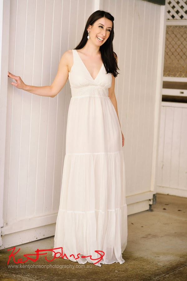 Vintage style, Vee neckline light white cotton wedding dress, model laughing. Photographed by Kent Johnson.