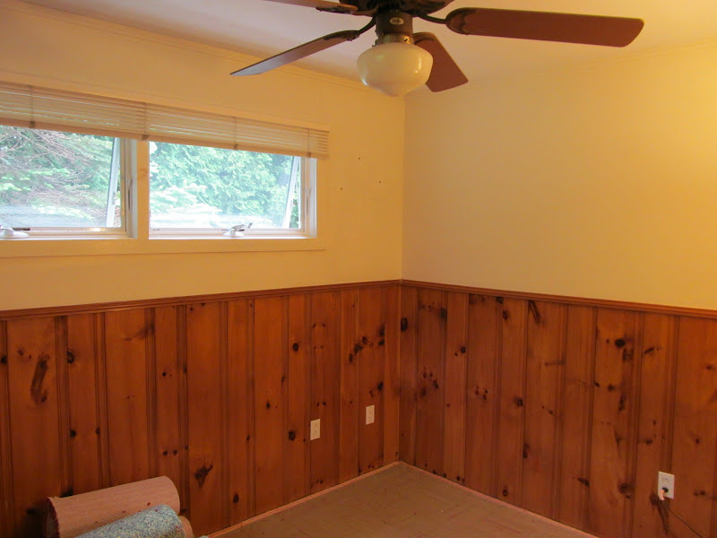 Lovely beasts guest room makeover with painted wood paneling for Wood paneling painted white
