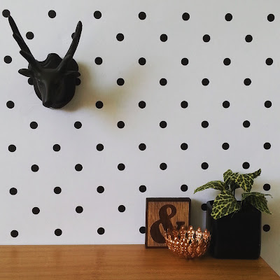 Modern dolls' house miniature scene with a black stag head mounted on a spotty wall behind a desk displaying a plant in a black pot, a bronze bowl and a wooden ampersand plaque.