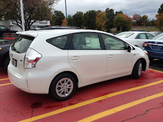 White Toyota Prius v hybrid wagon in a parking spot