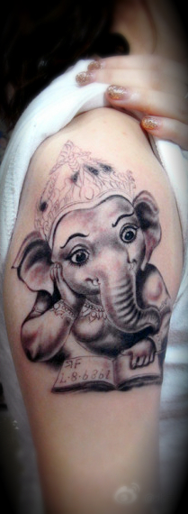 An arm  tattoo featuring humanized elephant queen reading a book