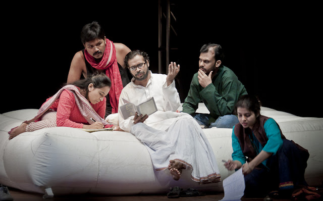 Is it possible to keep the conflicts out of a household when the society outside is crumbling under communal tensions? This is the subject of the new play by the National School of Drama. The story revolves a secular household where the wife is a Hindu and the husband, a Muslim. They live as tenants with Daddu and his son, Sharad. The members of the household live in harmony like many other households with laughter and love echoing from every corner, from the Madhu-Malati adorned windows to the white, neutral diwan. The lady in the front is Ipshita Chakraborty, the narrator who also plays the writer. The man in white dhoti-kurta is the actor Jagannath Seth who plays Daddu. The lady next to him is Sajida, who plays Shruti. The man behind her is Palash Protim Mech, who played Hanif and the man in green is Punj Prakash, who plays Sharad.
