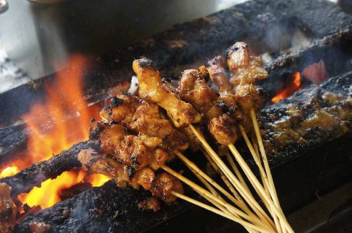 Chicken satay cooking over fire in Kajang, Malaysia - featured on SeasonWithSpice.com