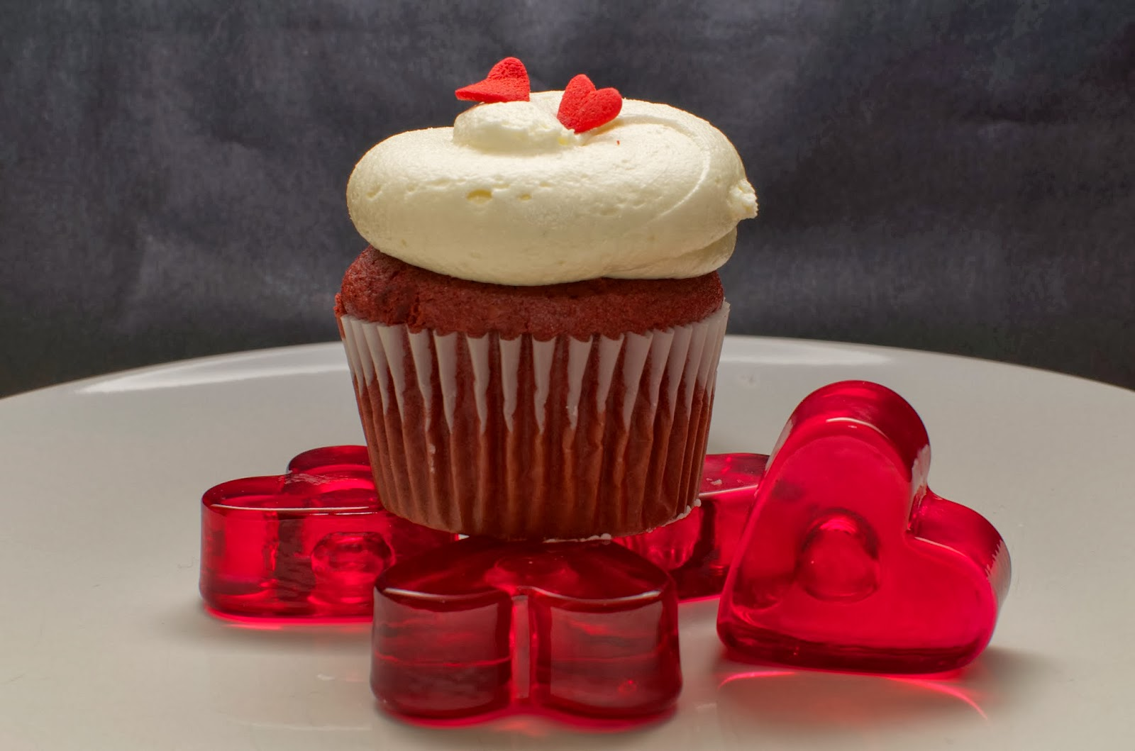 Red velvet cupcake decorated with red hearts sitting on top of heart shaped candle holders