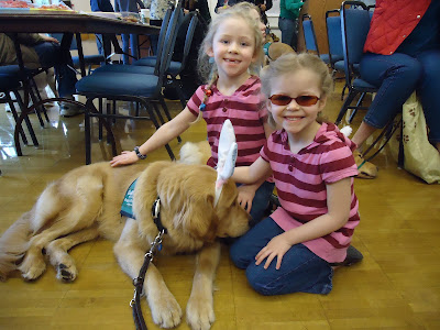 two young girls enjoy the company of a Golden puppy