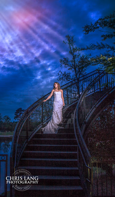 Dramatic wedding picture of bride standing on spiral stair case at River Landing. Majestic blue sky with sun ray coming through clouds onto the bride in her wedding dress.