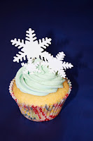 Lemon cupcakes topped with a pale blue buttercream swirl and fondant snowflakes