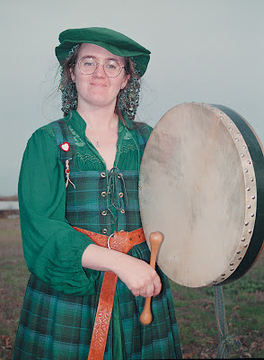 Cynthia Parkhill in green Renaissance costume with Irish frame drum