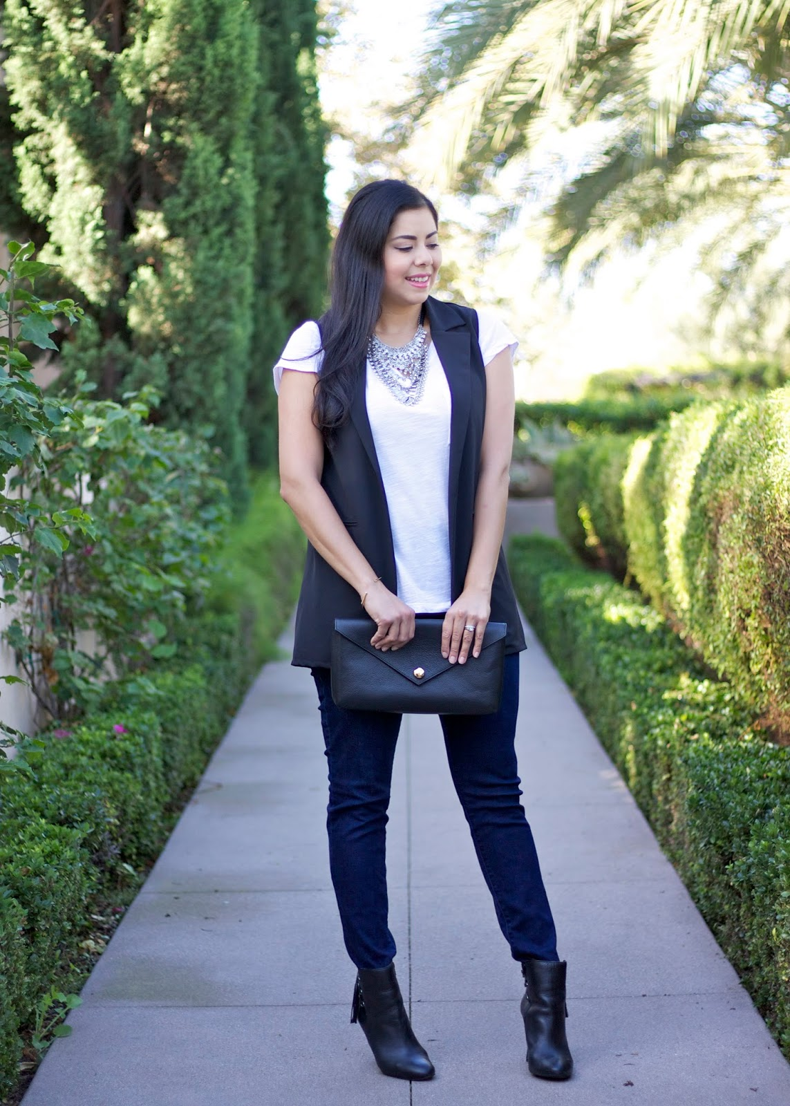 how to wear a longline vest, vest with jeans, black clutch and black boots, linell ellis clutch