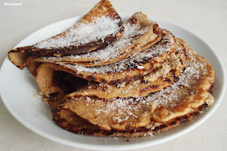Walnut rum vanilla filled pancakes on a plate with grated coconut on to