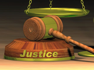 The word justice written on a gavel with scales of justice in the background.