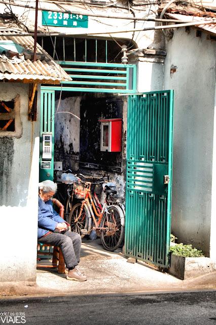 señora durmiendo en una calle de shanghai
