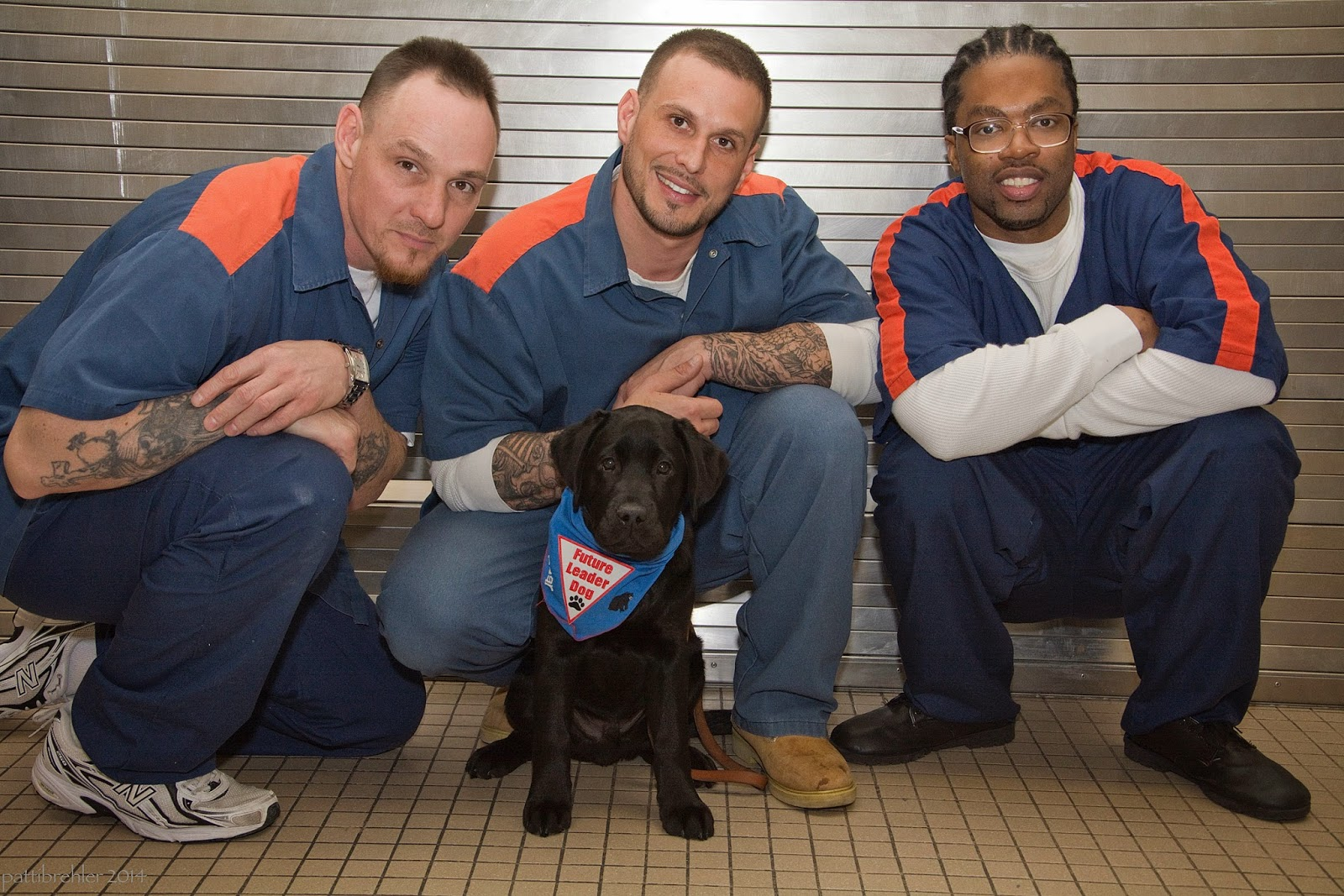 Three men are squatting in front of a steel wall on a tile floor. A young black lab puppy is sitting in front of the middle man, looking at the camera. The puppy is wearing a blue Future Leader  dog bandana. The men have their arms resting on their knees and are smiling at the camera. The man on the right is an african american and is wearing glasses.