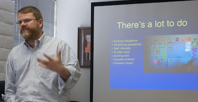 Patrick Ball giving a powerpoint presentation, the slide on the screen behind him entitled There's a Lot to Do