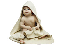 A light skinned naked baby of unknown gender sitting up, wearing an off-white hood that extends like a combination cape/hood/towel so that the baby is sitting on it. The baby is also holding an off-white towel or blanket.