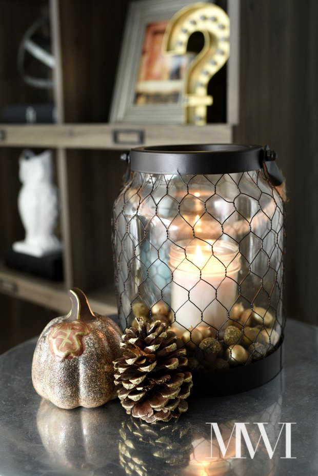 Lanterns are an easy way to decorate small end tables and spaces. This blogger adds in vase filler and a scented candle for a beautiful fall vignette.