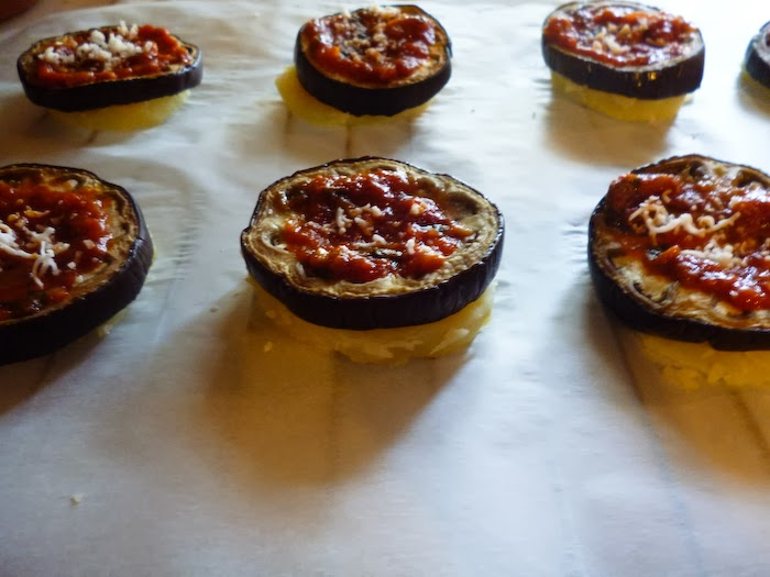 Building the moussaka tower step 1: one slice of potato, one slice of eggplant above and tomato sauce and cheese on top