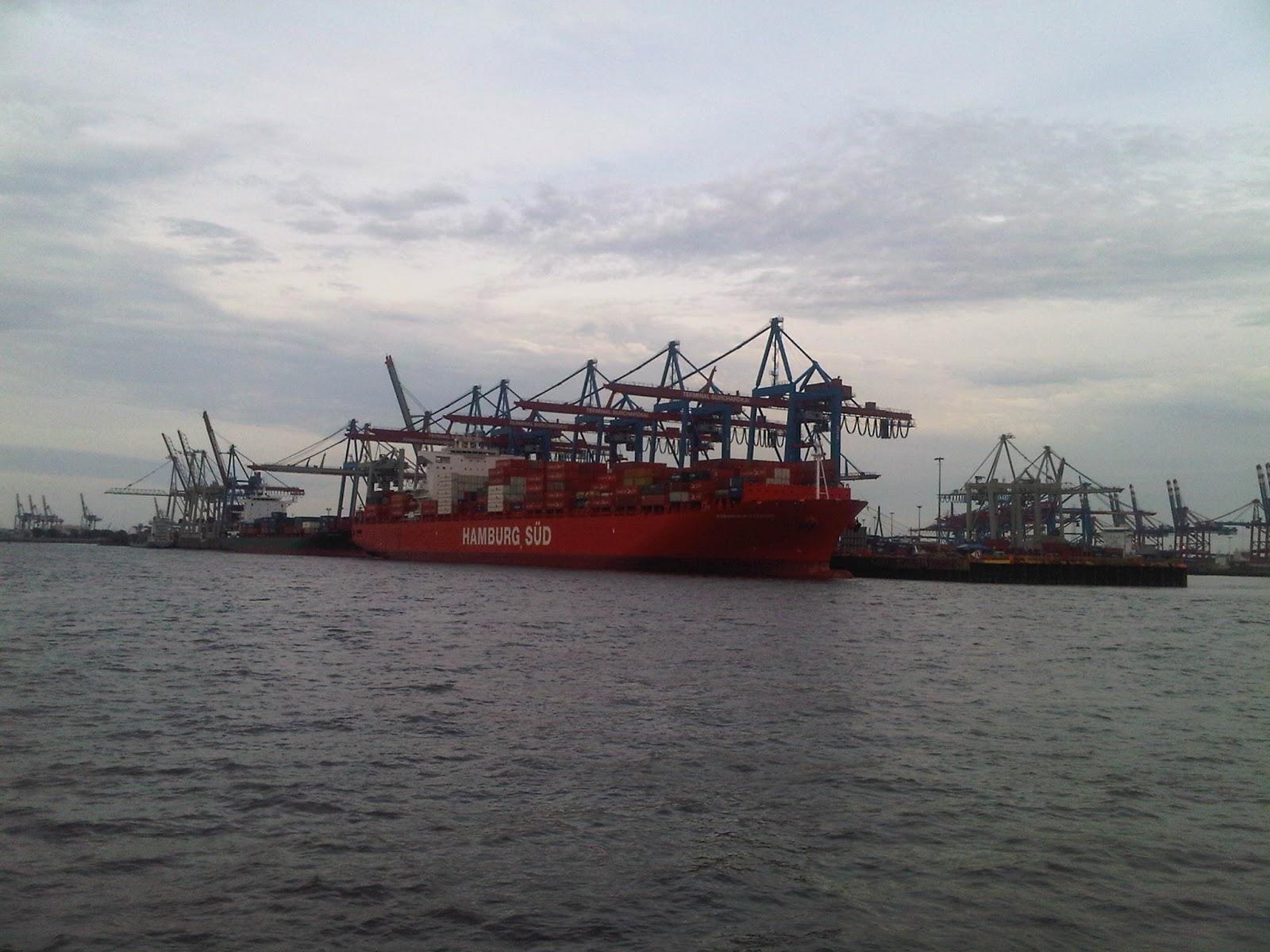 Container-Frachter Hamburg Süd am Container-Hafen. Wasser, roter Frachter, Kräne