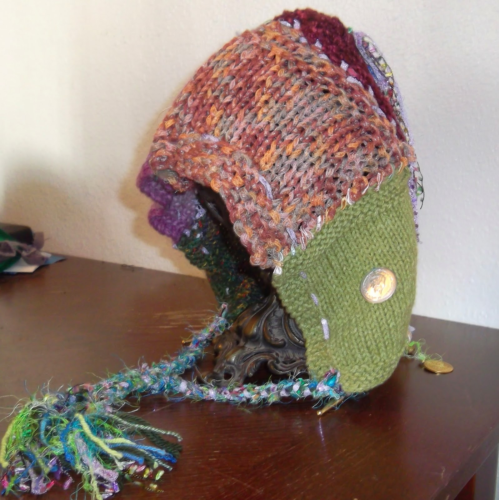 Knit swatches in varying colors, assembled into a hood that is draped over a round candle-holder on base. The hood's lower corners have braided ties that are made out of a variety of yarns. Coins and bells are fastened to the ends of streamers that hang from the hood's upper point.